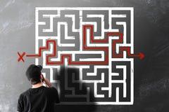 Homme regardant le dessin de craie du labyrinthe de labyrinthe sur le tableau noir photo libre de droits