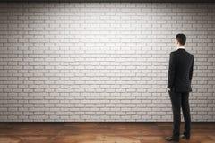 Homme regardant le mur de briques vide Photos stock