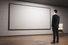 Homme regardant le panneau d'affichage vide Image stock