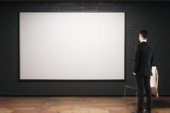 Homme regardant le panneau d'affichage vide Photo stock