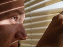 Homme regardant par des abat-jour Images libres de droits