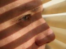 Homme regardant par des abat-jour Image libre de droits