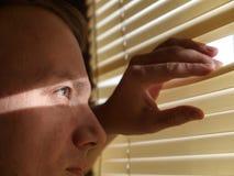 Homme regardant par des abat-jour Photographie stock libre de droits