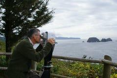 Homme regardant par des jumelles photographie stock libre de droits
