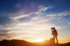 Homme regardant par des jumelles le coucher du soleil Image stock