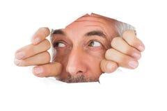 Homme regardant par le papier déchiré Image stock