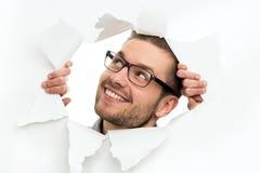 Homme regardant par le trou en papier photographie stock libre de droits