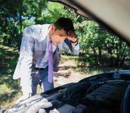 Homme regardant sous le capot de la voiture Photos stock