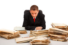 Homme regardant un bon nombre de documents Image stock