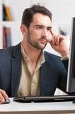 Homme regardant un moniteur d'ordinateur Photos libres de droits
