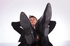 Homme Relaxed avec des pattes sur le bureau photographie stock libre de droits