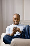 Homme Relaxed utilisant l'organisateur électronique Photographie stock