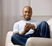 Homme Relaxed utilisant l'organisateur électronique Photographie stock libre de droits