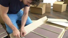 Homme remontant des meubles d'Assemblée d'individu dans la nouvelle maison banque de vidéos