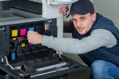 Homme remplaçant des cartouches d'encre dans le photocopieur photo libre de droits