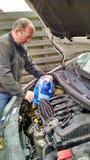 Homme remplissant le fluide de lavage de pare-brise dans la voiture Images stock