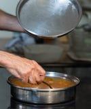 Homme remuant la casserole sur le dessus de fourneau Photo stock