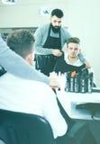 Homme rendant le client confortable avant coupe de cheveux Photo stock
