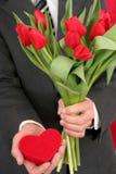 Homme retenant le cadre et les fleurs en forme de coeur Image libre de droits