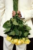 Homme retenant les roses jaunes Image libre de droits