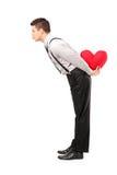 Homme retenant un coeur et donnant des baisers Photos libres de droits