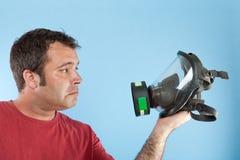 Homme retenant un masque de gaz Image stock
