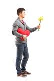 Homme retenant un objet en forme de coeur et des fleurs Photo stock