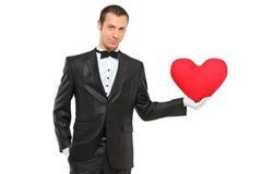 Homme retenant un oreiller en forme de coeur rouge Photo stock