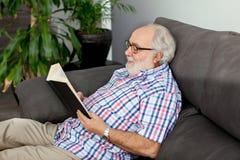 Homme retiré affichant un livre Photos libres de droits