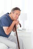 Homme retiré avec son bâton de marche Image stock