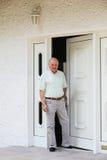 Homme retiré dans la porte de sa maison Photographie stock libre de droits
