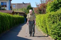 Homme retiré par aîné marchant sur des béquilles Image libre de droits