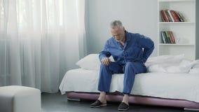 Homme retiré s'asseyant dans le lit et le dos, la santé et la maladie terribles se sentants de douleur dedans Image stock
