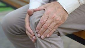 Homme retiré se levant à peine du banc, douleur dans les joints, problèmes avec des genoux banque de vidéos