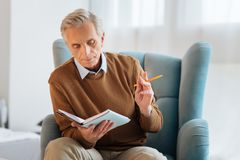 Homme retiré serein avec le crayon pensant et faisant des notes Photo stock