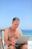 Homme retiré travaillant sur son ordinateur portatif sur la plage Images libres de droits