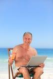 Homme retiré travaillant sur son ordinateur portatif sur la plage Image stock