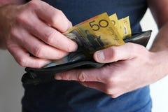 Homme retirant l'argent liquide du portefeuille Photographie stock