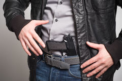 Homme retirant une arme à feu prête Photos libres de droits