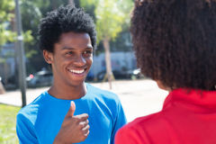 Homme riant d'afro-américain montrant le pouce à la femme Photos stock