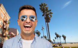Homme riant dans des lunettes de soleil au-dessus de plage de Venise photos stock