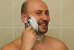 Homme riant heureux rasant son visage photos libres de droits