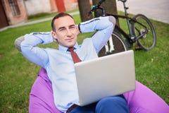 Homme riche ayant le repos avec l'ordinateur dehors Photo libre de droits