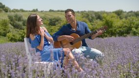 Homme romantique chantant une sérénade à la femme avec la guitare dehors clips vidéos