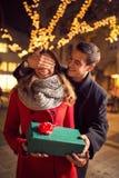 Homme romantique se tenant derrière la femme avec le cadeau sur la rue avec Chri Photographie stock