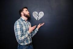 Homme romantique triste tenant le coeur brisé dessiné au-dessus du fond de tableau noir Photo stock