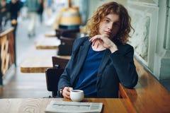 Homme rougeâtre de hippie de portrait avec le coffe et le journal photo libre de droits