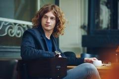 Homme rougeâtre intéressant de portrait posant avec du café photo stock
