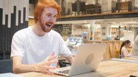 Homme roux enthousiaste de barbe célébrant le succès, se reposant en café photo libre de droits
