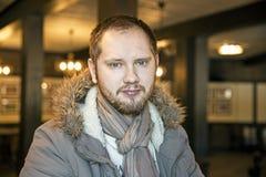 Homme russe avec la barbe se reposant à l'intérieur dans un manteau Photo libre de droits